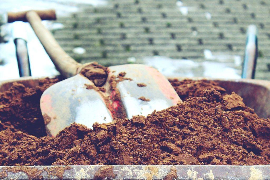 pioche posée dans une brouette remplie de terre