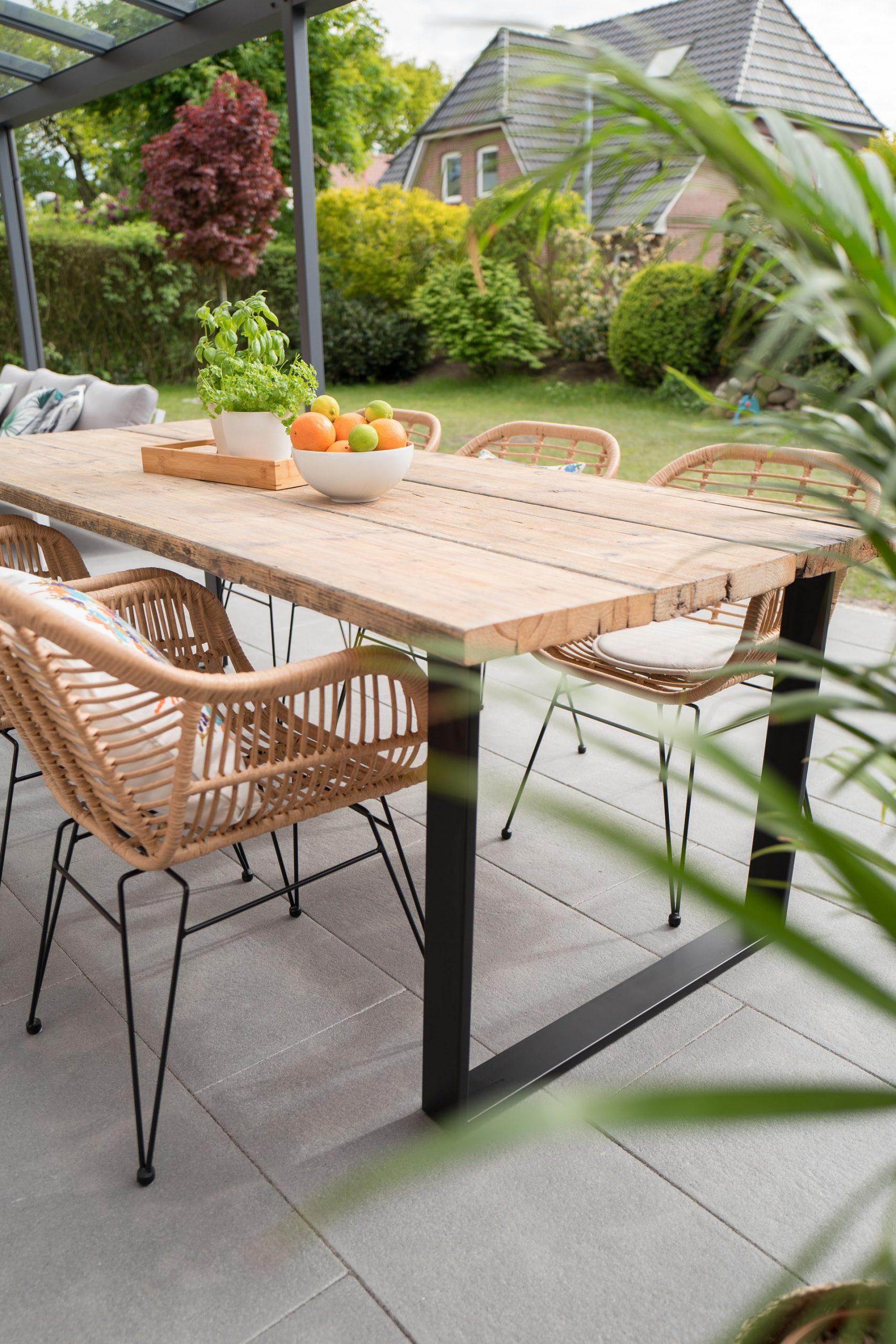 table et chaises en bois posées sur une terrasse carrelée